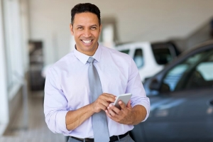 handsome middle aged man using smart phone at car dealership